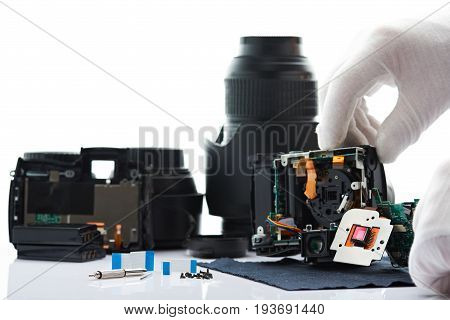 Fixing modern photo camera background. Closeup of tools and photo gear isolated on white background