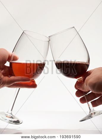 Toast of two wine glasses close-up isolated on white background. Cheers of two red wine glasses