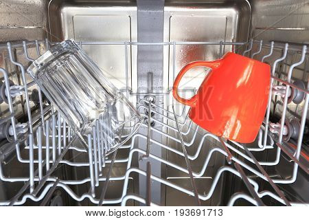 Wet stainless steel dishwasher interior. Cups in dishwasher machine