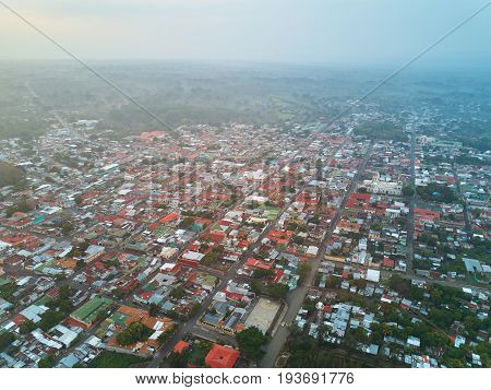 Small city blocks aerial view in morning sunrise light time. Drone view on little town