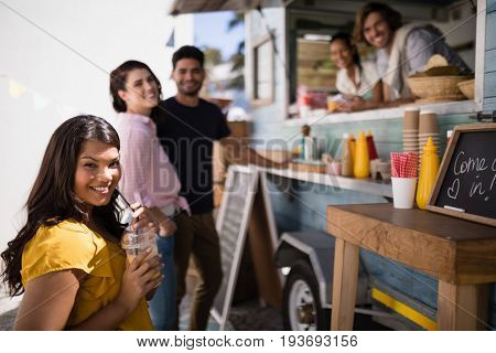 Portrait of friends smiling at counter in food truck van