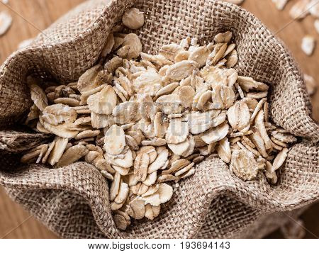 Oat Flakes Cereal In Burlap Sack On Wooden Table.