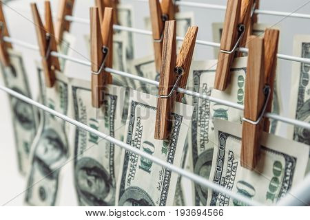 Money laundering concept. Dryer and banknotes on clothespins. American hundred dollar bills hanging to be dry and clean cash