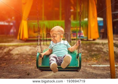 Little Blonde Boy Having Fun At The Playground. Child Kid Playing On A Swing Outdoor. Happy Active C