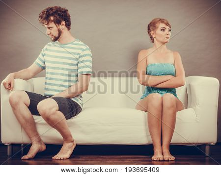 Bad relationship concept. Man and woman in disagreement. Young couple after quarrel sitting offended on couch