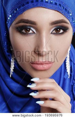 Gorgeous Young East Woman face portrait in hijab. Beauty Model Girl with bright eyebrows, perfect make-up, touching her face. Traditional. Isolated on black background. Smokey.Jewelry on her face.Studio