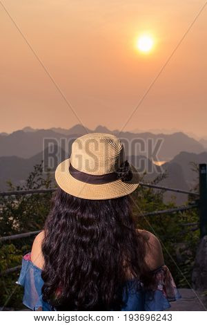 Girl enjoying sunset view from Cannon fort viewpoint in Cat ba Vietnam
