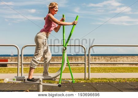 Active young woman exercising on elliptical trainer machine. Fit sporty girl in training suit working out at outdoor gym. Sport fitness and healthy lifestyle concept.