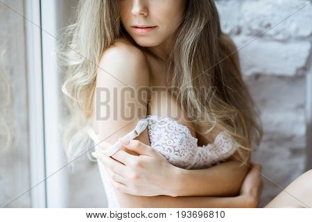 Female portrait of cute lady in white bra indoors. Close up beautiful sexy model girl in elegant pose. Closeup beauty blonde woman with hairstyle