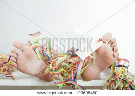 Close Up Of Bare Feet With Toe Tag And Ribbons
