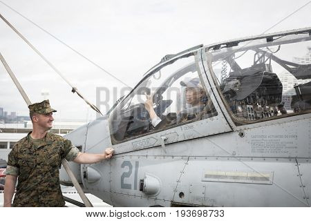 Ship Tour USS Kearsarge (LHD 3) Wasp-class amphibious assault ship: Visitor sits in cockpit of USMC AH-1W Cobra Marine Light Attack Helicopter HMLA-16. Fleet Week NEW YORK MAY 25 2017.