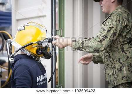 Ship Tour USS Kearsarge (LHD 3) Wasp-class amphibious assault ship: U.S. Navy Seabee personnel helps an unidentified boy put on dive helmet, flight deck. Fleet Week NEW YORK MAY 25 2017.