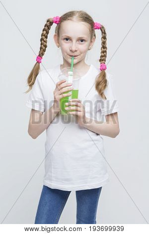 Kids Lifestyle Concepts. Portrait of Pretty Smiling Caucasian Blond Girl With Long Pigtails Holding Cup and Drinking Green Juice Through Straw. Vertical Image Composition