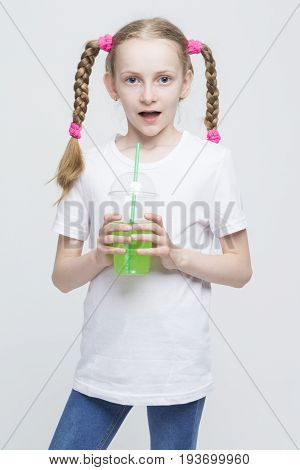 Portrait of Surprised Pretty Caucasian Blond Girl With Long Pigtails Holding Cup and Drinking Green Juice Through Straw. Vertical Image Composition