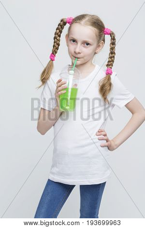 Kids Lifestyle Concepts. Portrait of Pretty Smiling Caucasian Blond Girl With Long Pigtails Holding Cup and Drinking Green Juice Through Straw. Vertical Shot
