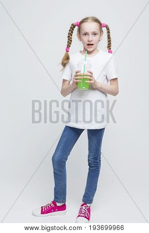 Full Length Portrait of Surprised Pretty Caucasian Blond Girl With Long Pigtails Holding Cup and Drinking Green Juice Through Straw. Vertical Image Composition