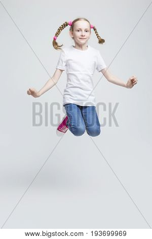 Portrait of Smiling Caucasian Blond Girl With Pigtails Making a High Jump in Studio. Against White Background. Vertical Image