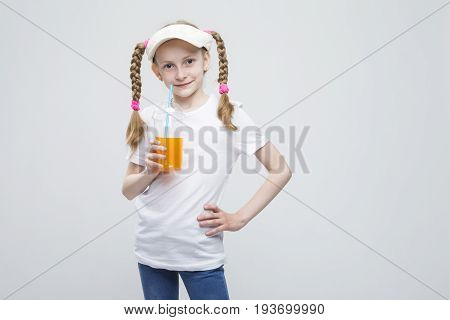 Portrait of Happy Smiling Caucasian Blond Girl in Visor Holding Cup of Juice against White. Horizontal Image