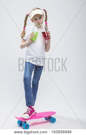 Kids Concepts. Portrait of Little Caucasian Blond Girl in Visor Posing on Pennyboard With Two Cups of Juice and Straw. Against White. Vertical Shot