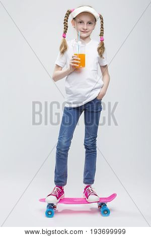 Full Length Portrait of Happy Caucasian Blond Girl in Visor Ballancing on Pennyboard With Cup of Juice with Straw.Against White. Vertical Image Composition