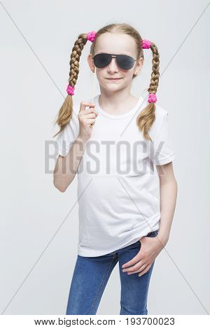 Kids Ideas and Concepts. Portrait of Positive Caucasian Blond Girl With Pigtails Posing with Artistic Spectacles Against White Background. Vertical Image