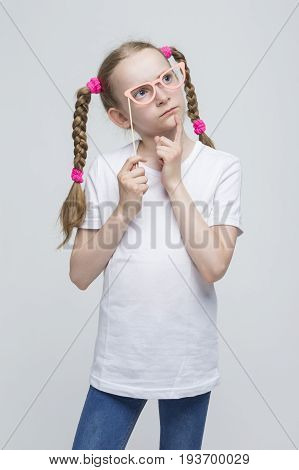 Portrait of Thinking Caucasian Blond Girl With Pigtails Posing with Artistic Spectacles Against White Background. Vertical Image