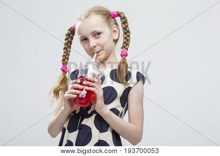 Portrait Of Smiling Caucasian LIttle Girl With Pigtails Standing in Polka Dot Dress with Cup of Red Juice. Against White. Drinking Through Straw. Horizontal Shot