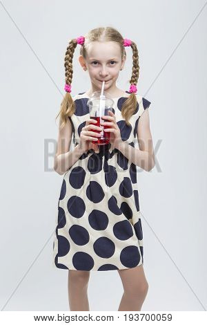 Portrait Of Smiling Caucasian LIttle Girl With Pigtails Standing in Polka Dot Dress with Cup of Red Juice. Against White. Drinking Through Straw. Vertical Image