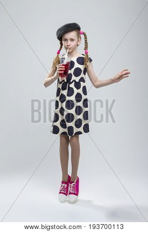 Full Length Portrait of Jumping Caucasian Girl With Pigtails Posing in Gray Velvel Cap and Polka Dot Dress with Cup of Red Juice. Drinking Through Straw. Against White. Vertical Shot