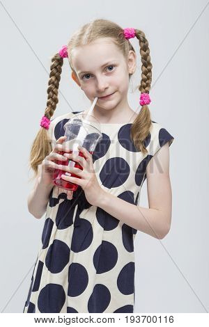 Kids Concepts. Closeup Portrait of Beautiful Caucasian Blond Girl With Pigtails Posing in Polka Dot Dress Against White. Holding Cup with Red Juice and Straw. Vertical Image Composition