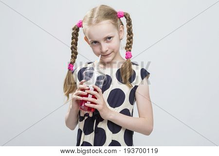 Kids Concepts. Closeup Portrait of Curious Caucasian Blond Girl With Pigtails Posing in Polka Dot Dress Against White. Holding Cup with Red Juice and Straw. Horizontal Image