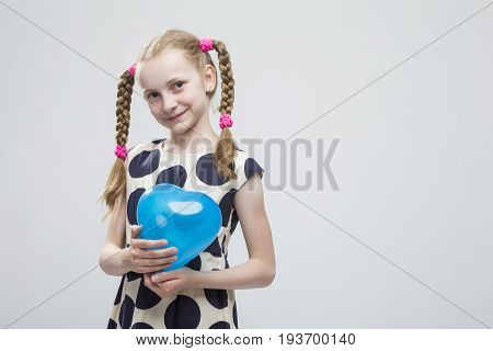 Portrait of Funny Caucasian Blond Girl With Pigtails Posing in Polka Dot Dress Against White. Holding Blue Air Balloon.Horizontal Image Composition