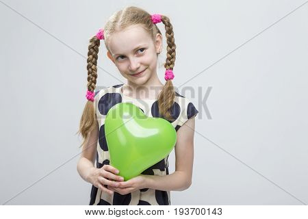 Portrait of Curious Funny Caucasian Blond Girl With Pigtails Posing in Polka Dot Dress Against White. Holding Green Air Balloon. Horizontal Image Composition