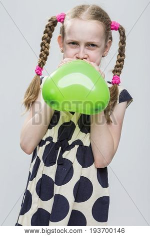 Portrait of Funny Caucasian Blond Girl With Pigtails Posing in Polka Dot Dress Against White. Blowing Up Green Heart Shaped Air Balloon. Vertical Image
