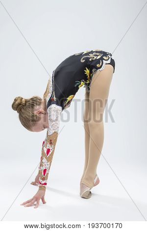 Sport Ideas. Young Caucasian Female Rhythmic Gymnast Athlete In Professional Competitive Suit Doing Backbend Stretching Exercise While Posing in Studio Against White. Vertical Image