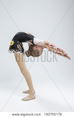 Sport Ideas. Young Caucasian Female Rhythmic Gymnast Athlete In Professional Competitive Suit Doing Backbend Stretching Exercise While Posing in Studio Against White. Vertical Image Composition