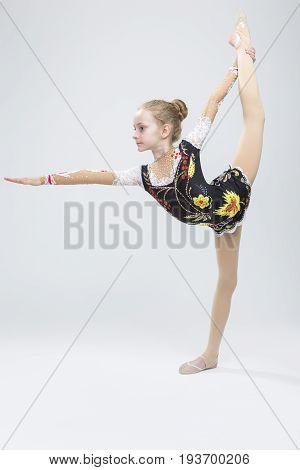 Caucasian Female Rhythmic Gymnast Athlete In Professional Competitive Suit Doing Vertical Split Exercise While Posing in Studio Against White. Vertical Orientation