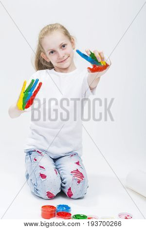 Kids Concepts. Portrait of Smiling Young Girl Showing Messy Colorful Hands Brightly Painted During Paint Craft. Against White Background. Focus on Hands. Vertical Shot