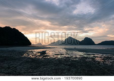 EL NIDO, PALAWAN, PHILIPPINES - MARCH 29, 2017: Wide angle view of sunset with a boat silhouette at Las Cabanas Beach.