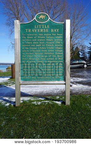 PETOSKEY, MICHIGAN / UNITED STATES - SEPTEMBER 22, 2016: A Michigan Historical Commission sign, in Sunset Park, describes the history of the Little Traverse Bay area.