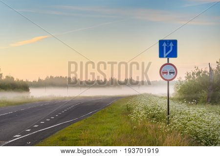 Foggy Sunrise On The Road Among Fields With Trees And Signs Overtaking Is Forbidden, And The Splitti