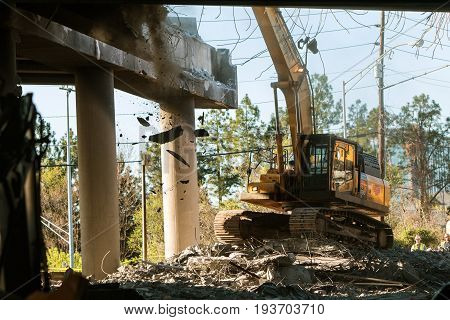 ATLANTA, GA - APRIL 2017:  A crane knocks down a section of I-85 South just imploded following the collapse of the I-85 North bridge from a fire in Atlanta GA on April 1 2017.