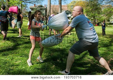 ATLANTA, GA - APRIL 2017:  A man and girl try to hit each other with pillows on International Pillow Fight Day in Grant Park in Atlanta GA on April 1 2017.
