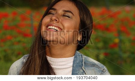 Hispanic Teen Girl Laughing with Flowers in Background