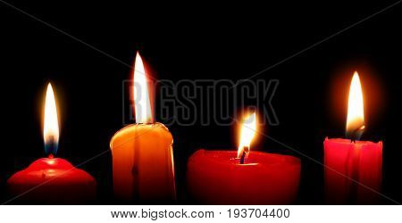 Four red burning candles against black background