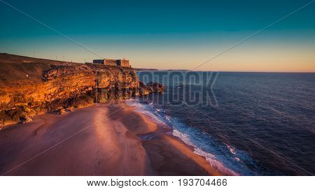 Aerial view of ocean and Nazare lighthouse at sunset, Portugal