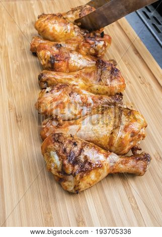Barbecued Chicken Drumsticks arranged on a bamboo cutting board