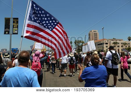 Impeachment March in San Diego, California on July 2, 2017 with large flag and people holding signs.
