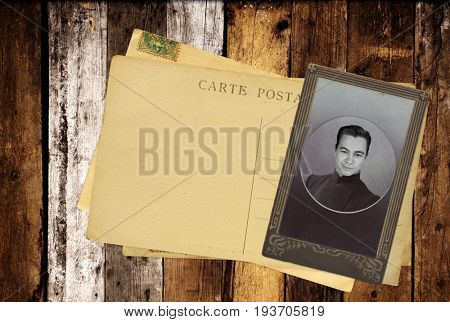 Vintage post cards and retro photo on old wooden planks. Inscription on the card - carte postale - postcard in french