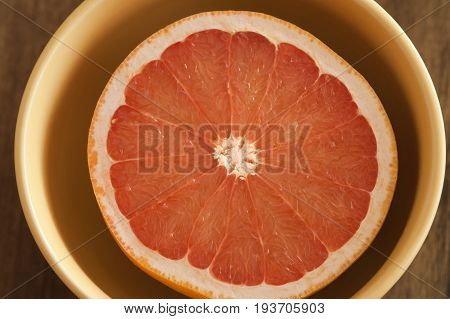 Fresh pink grapefruit half served in a bowl for breakfast viewed from overhead in a healthy diet concept